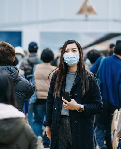 Woman in a protective mask, standing out from a crowd